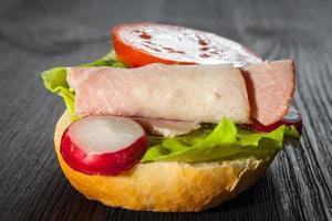 ham, salade onderzeese sandwich van vers gesneden stokbrood foto