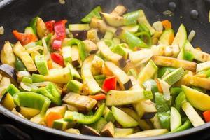 veel verschillende groenten koken in de koekenpan foto