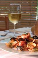 garnaalschotel met glas witte wijn - het knippen weg foto
