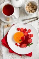 sinaasappelterrine met aardbeiensaus en aardbeien. foto