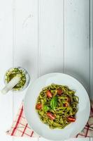 spinazie tagliatelle met basilicumpesto en mini tomaten foto