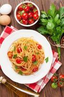 spaghetti pasta met tomaten en peterselie foto
