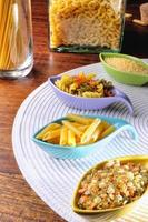 ongekookte pasta in keramische containers op een wit tafellaken foto