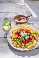smakelijke pasta penne met tomatensaus en parmezaan foto