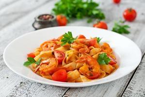 fettuccine pasta met garnalen, tomaten en kruiden foto