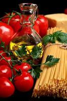 rauwe pasta geïsoleerd op zwarte tomaten, olijfolie, knoflook verti foto