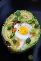 eieren gebakken in avocado gegarneerd met groene uien