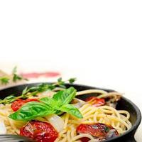 spaghetti pasta met gebakken cherrytomaatjes en basilicum foto