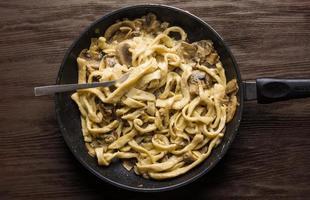 huisgemaakte fettuccini pasta in roomsaus met champignons foto
