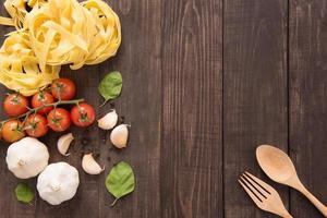 pasta ingrediënten. tomaat, knoflook, peper en champignons op hout foto
