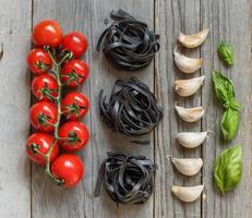 zwarte pasta met cherrytomaatjes, knoflook en basilicum foto
