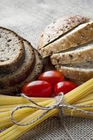 droge pasta en tomaten met gesneden brood op zak achtergrond foto