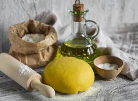 deeg om zelfgemaakte pasta te maken op een lichte houten achtergrond foto