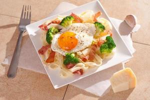 tagliatelle pasta met broccoli, prosciutto en gebakken ei. foto