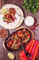 fajitas van varkensvlees met uien en gekleurde peper, geserveerd met tortilla