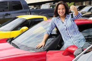 vrouw die sleutel van nieuwe sportwagen toont