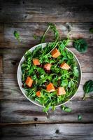 verse rucola en spinaziesalade met pompoen op rustieke pagina foto