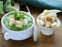 Groentesoep van broccoliroom met witte croutons en peterselie foto