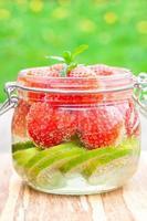 zelfgemaakte vruchtendrank met aardbeien limoen en munt op tafel foto