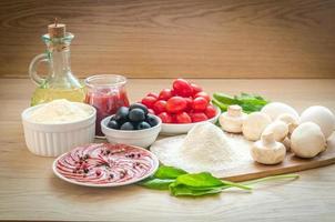 ingrediënten voor pizza op de houten achtergrond foto