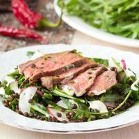 salade met gegrilde biefstuk, zwarte linzen, rucola, radijs
