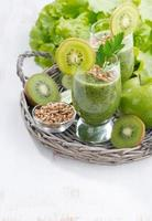 gezonde groene smoothie met spruiten en witte houten achtergrond foto