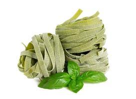 Italiaanse pasta tagliatelle met basilicum geïsoleerd op wit foto
