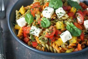 Italiaanse pasta met verse tomaten, kaas en spinazie foto