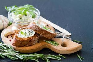 lookbrood op houten bord, rozemarijn, basilicum, knoflook, peper, foto