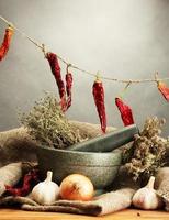 gedroogde kruiden in mortel en groenten op grijze achtergrond foto