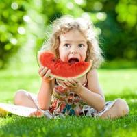 kind eet watermeloen buiten in het park foto