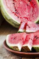 watermeloen segmenten op een kleiplaat foto