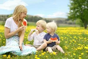 moeder en jonge kinderen die fruit in bloemenweide eten foto