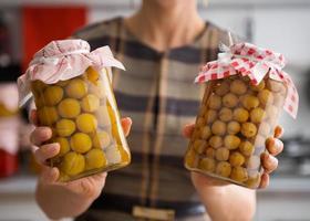 close-up van gele pruimen en kruisbessen in glazen potten