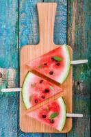 plakjes verse, sappige watermeloen op snijplank met munt foto