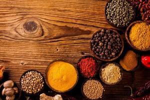 kleurrijke kruiden in houten kommen foto