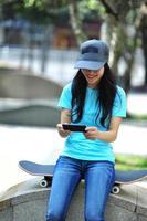 jonge vrouw skateboarder gebruiken haar mobiele telefoon foto