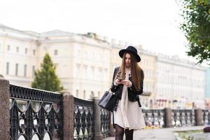 vrouwelijke student leest bericht op mobiele telefoon tijdens het wandelen foto