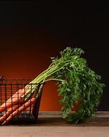 wortelen in draadmand met warme achtergrond foto