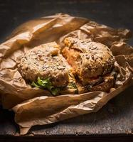 broodje met kip, kaas sla verfrommeld papier rustieke houten achtergrond