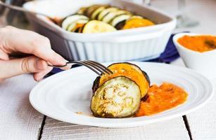 eet warme ratatouille in een vorksaus, hand foto