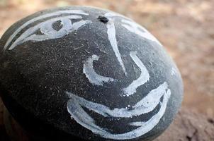 gezicht geschilderd op rots