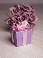 paarse bloemen en geschenkdoos met roze lint foto