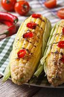 hete gegrilde maïs met chili pepers close-up. verticaal foto