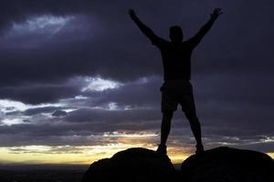 silhouet man met armen verhoogd in avondrood landschap foto