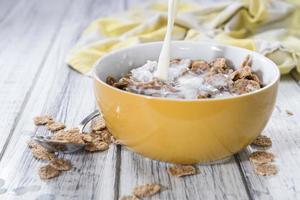 melk gieten in een kom met cornflakes foto