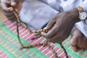 handen van een moslim man bidden met een rozenkrans kralen
