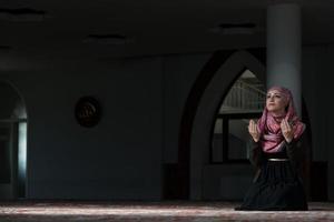 jonge moslimvrouw bidden in de moskee