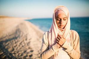 nederige moslimvrouw bidden op het strand. spirituele religieuze vrouw foto