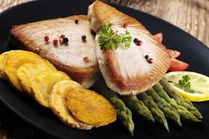 gegrilde tonijnsteak geserveerd op asperges met geroosterde zmieniakami